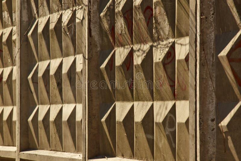 O diamante deu forma ao close-up concreto da cerca em um fundo escuro Fundo da estrutura imagens de stock