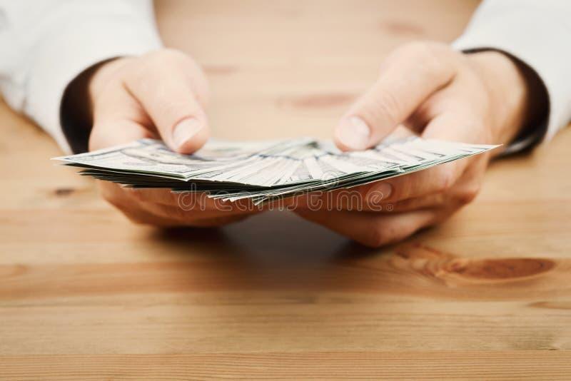 O dinheiro da contagem do homem desconta dentro sua mão A finança, economia, salário e doa o conceito imagens de stock