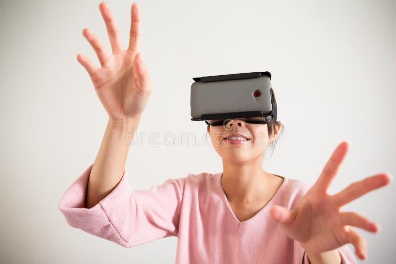 O dispositivo e a mão vestindo do vr da jovem mulher querem tocar no somrth foto de stock royalty free