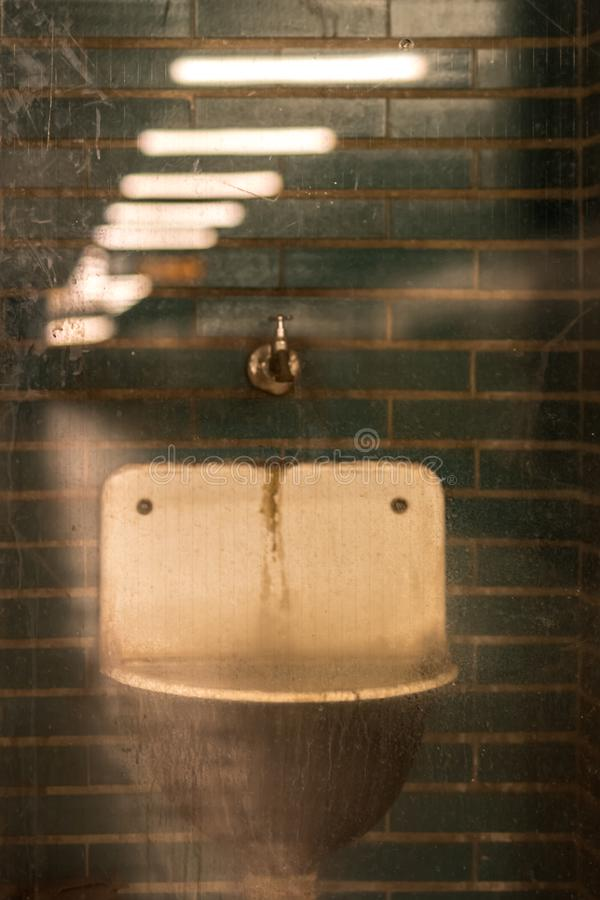 O dissipador velho na parede verde foto de stock
