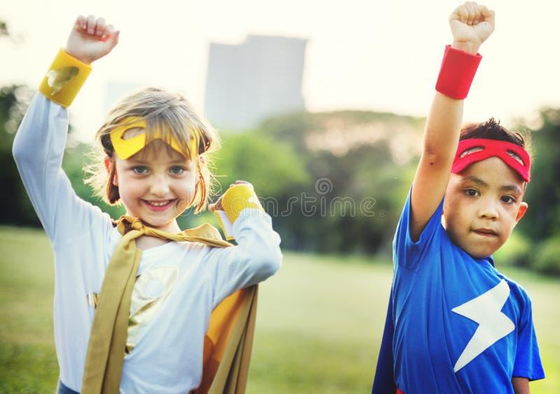 O divertimento dos super-herói das crianças traja o conceito do jogo fotos de stock royalty free