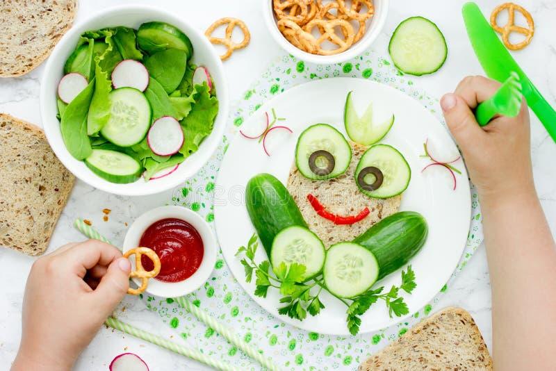 O divertimento e o alimento saudável para o sanduíche vegetal do pão das crianças deram forma ao franco fotografia de stock