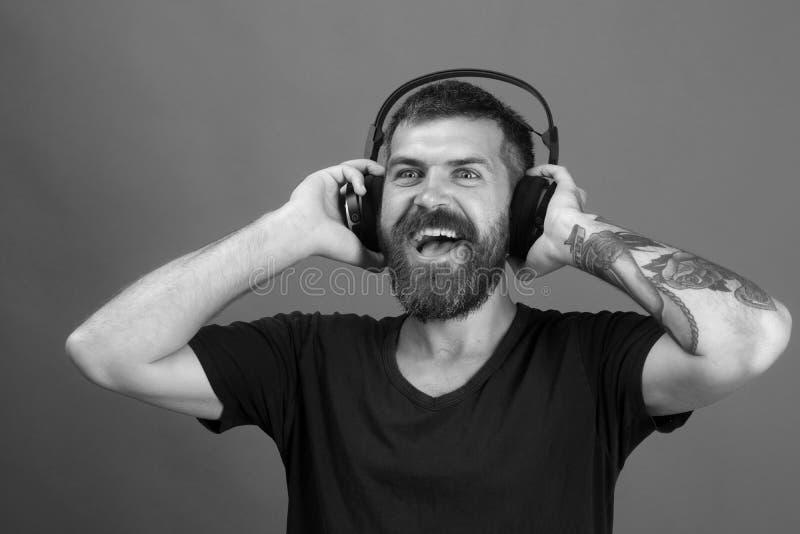 O DJ com barba veste fones de ouvido Relaxe e conceito da música Cantor com barba e a cara de sorriso foto de stock royalty free