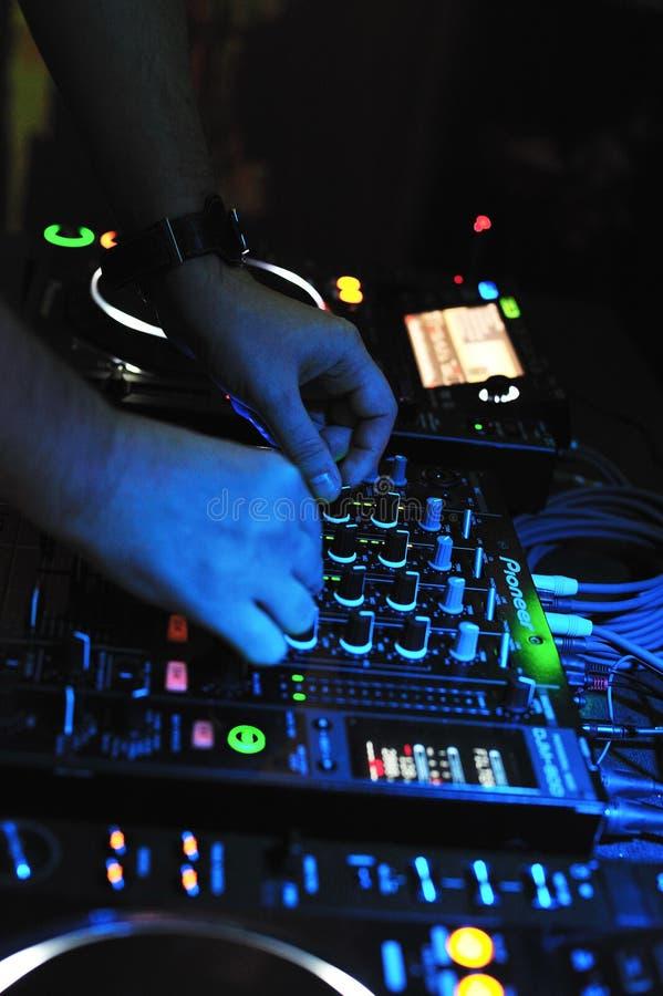 O DJ mistura e jogando com o misturador pioneiro e consola imagem de stock royalty free