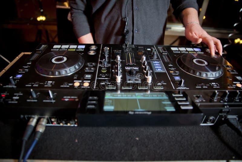 O DJ que joga o disco abriga a eletro música progressiva no concerto Mãos do DJ no equipamento O DJ joga a mistura no controlador fotos de stock royalty free