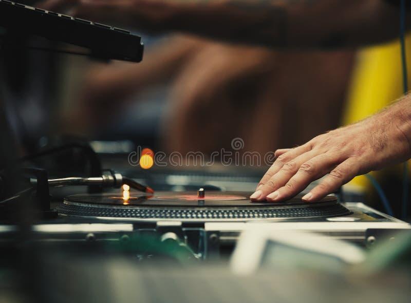 O DJ risca registros de vinil no jogador de registros da plataforma giratória imagem de stock royalty free