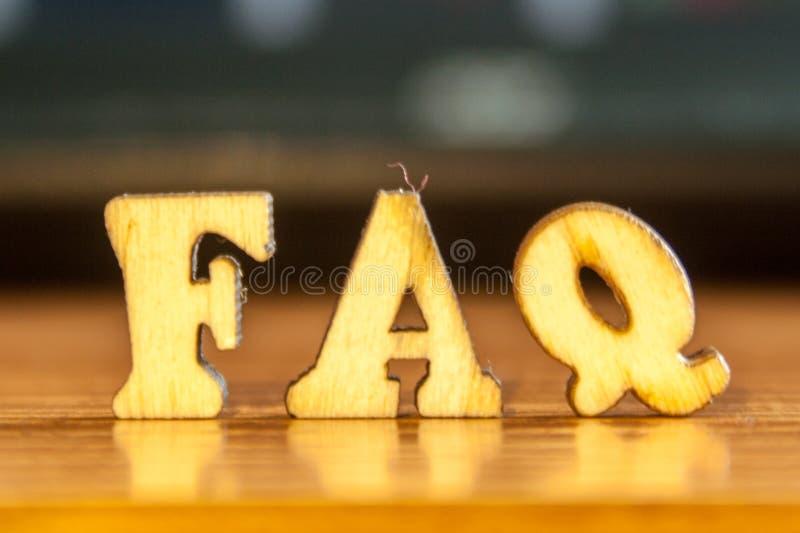 O ` do FAQ do ` da palavra feito de letras de madeira fotos de stock