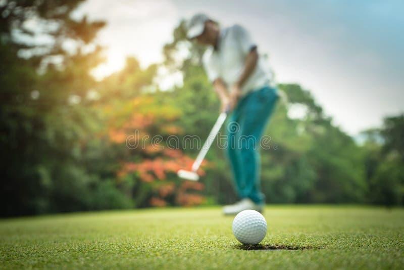A??o do jogador de golfe a ganhar ap?s por muito tempo ter posto a bola de golfe sobre o golfe verde fotografia de stock