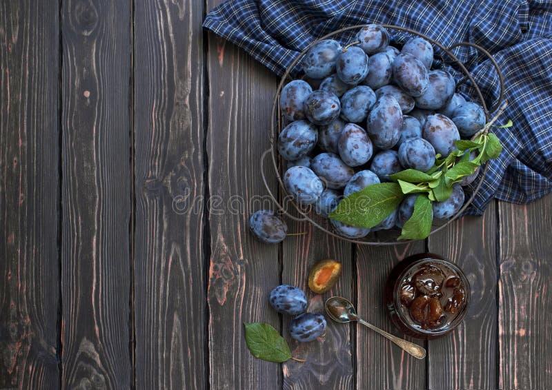O doce caseiro da ameixa em um frasco de vidro e as ameixas azuis frescas em uma bacia em um fundo de madeira rústico escuro com  imagem de stock