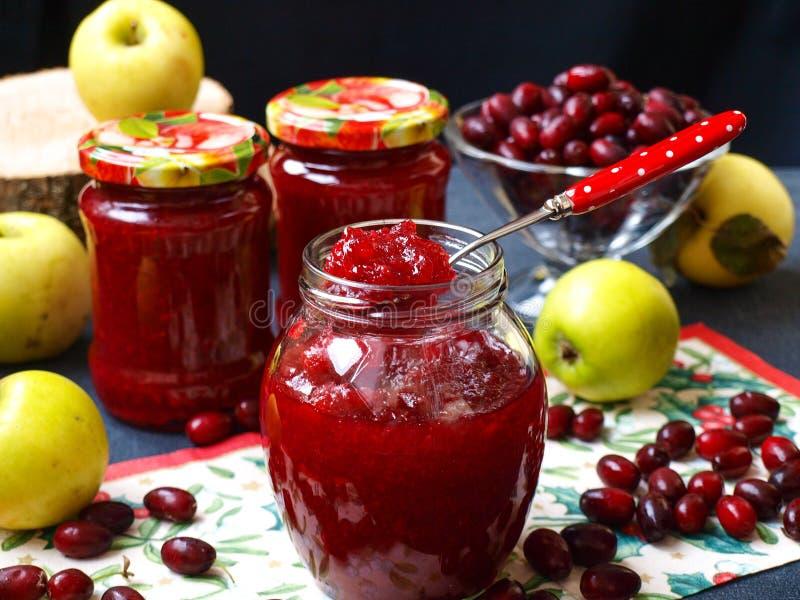 O doce caseiro dos cornisos e das maçãs é ficado situado nos frascos na tabela, um frasco está aberto fotos de stock