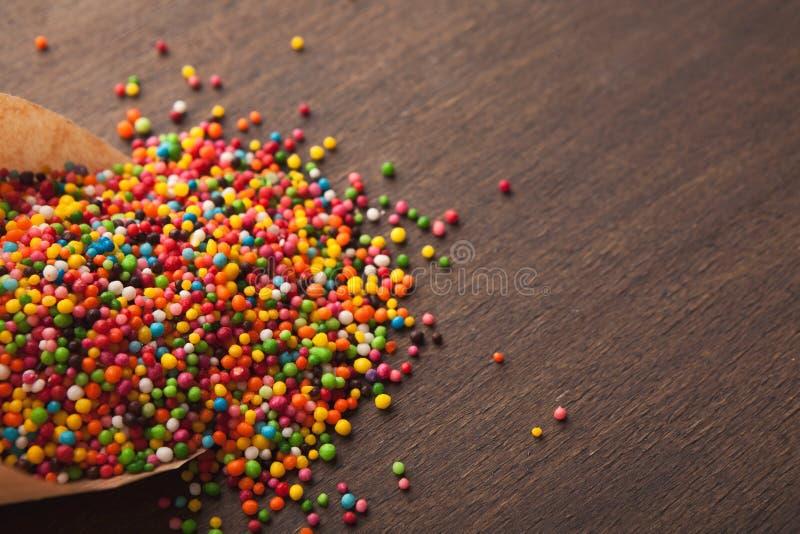 O doce colorido polvilha no fundo de madeira imagens de stock