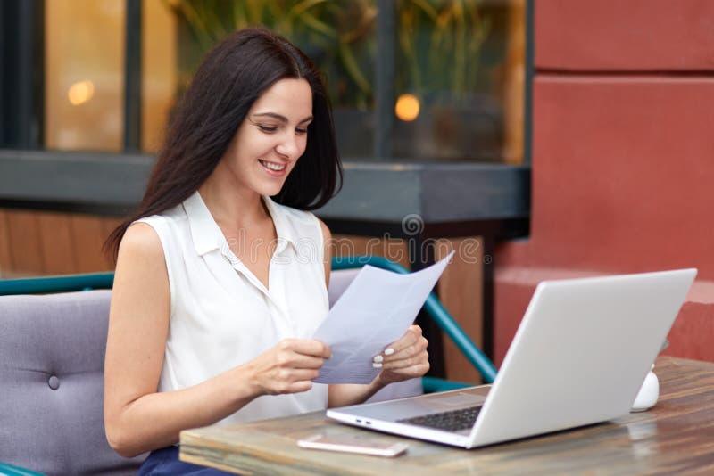 O documento de papel de cabelo escuro satisfeito dos estudos da mulher com a expressão contente, vestida na roupa formal elegante fotos de stock