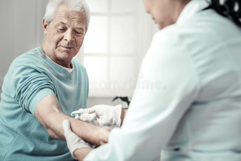 O doente envelheceu o homem que olha seu braço e que tem a injeção imagens de stock royalty free