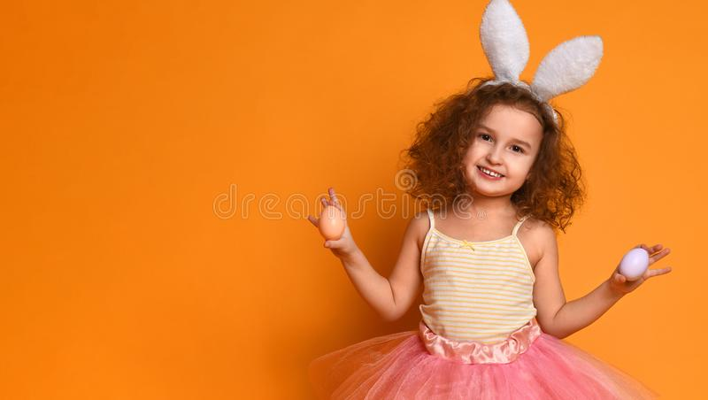 O?dos del conejito de la muchacha linda del peque?o ni?o que llevan el d?a de Pascua foto de archivo