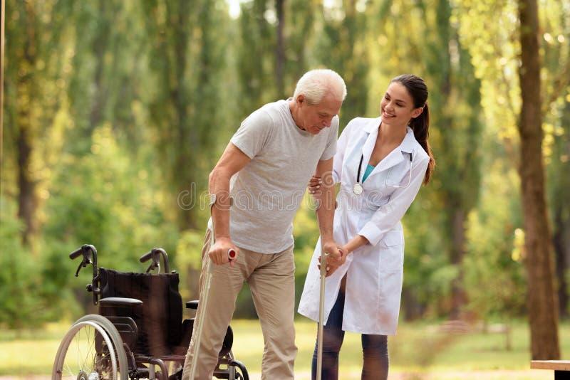 O doutor ajuda o ancião a estar em muletas Cadeira de rodas deixada atrás foto de stock