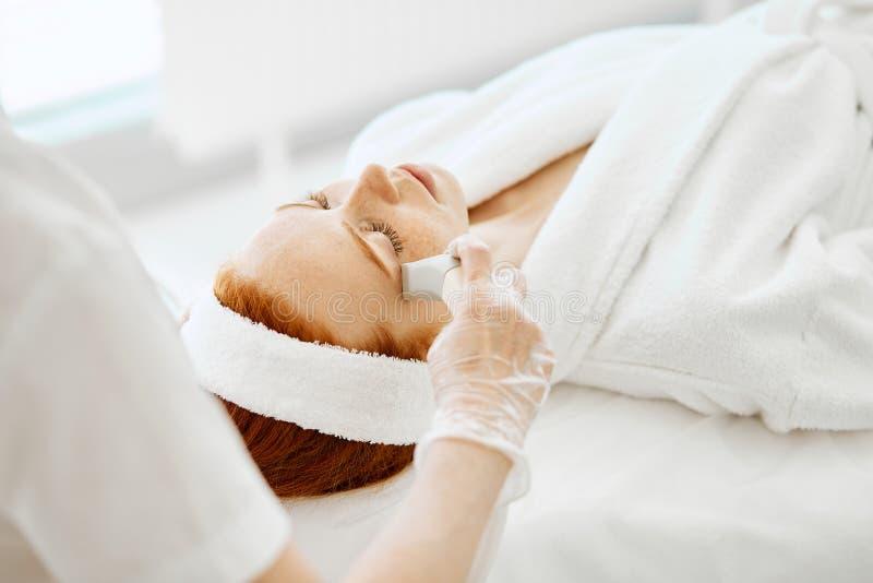O doutor aplica a hidro máscara do gel na mulher antes de fazer o tratamento do laser foto de stock royalty free