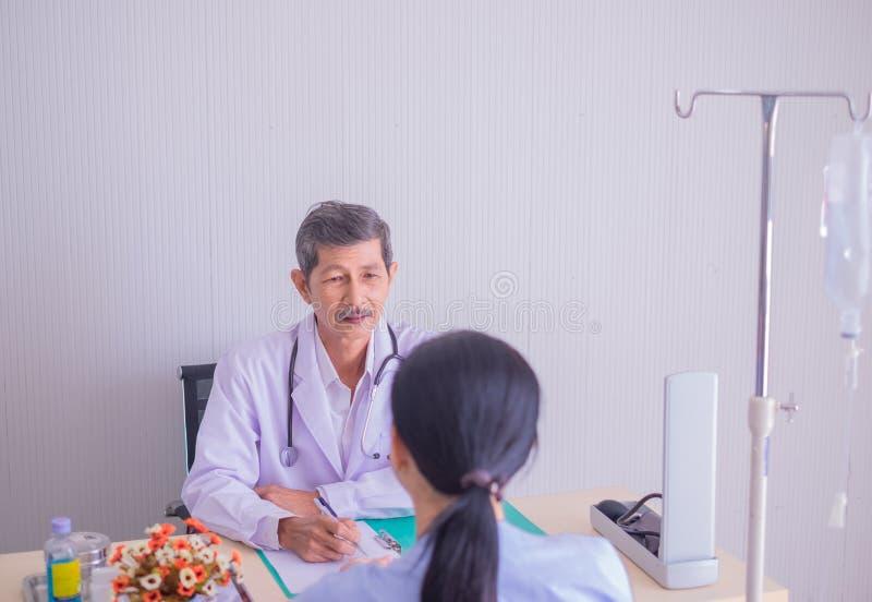 O doutor asiático do homem superior, falando dando o aconsultation explica o médico com paciente das mulheres fotografia de stock