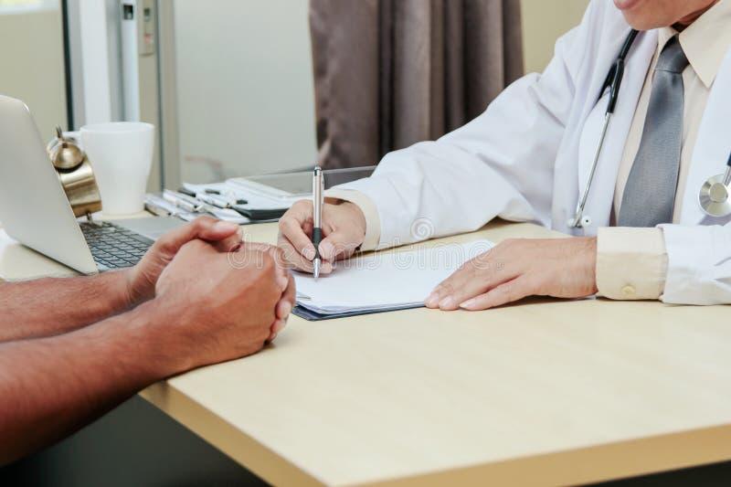 O doutor asiático que fala e que toma notas com paciente masculino consulta fotos de stock