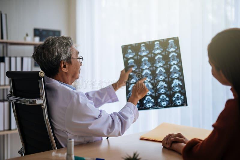 O doutor asiático superior examina a imagem de MRI para explicar ao paciente imagens de stock royalty free