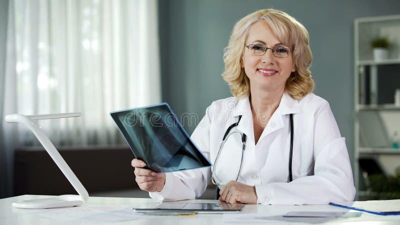 O doutor atrativo que guarda os pulmões pacientes faz a varredura, sorrindo in camera, diagnósticos fotografia de stock