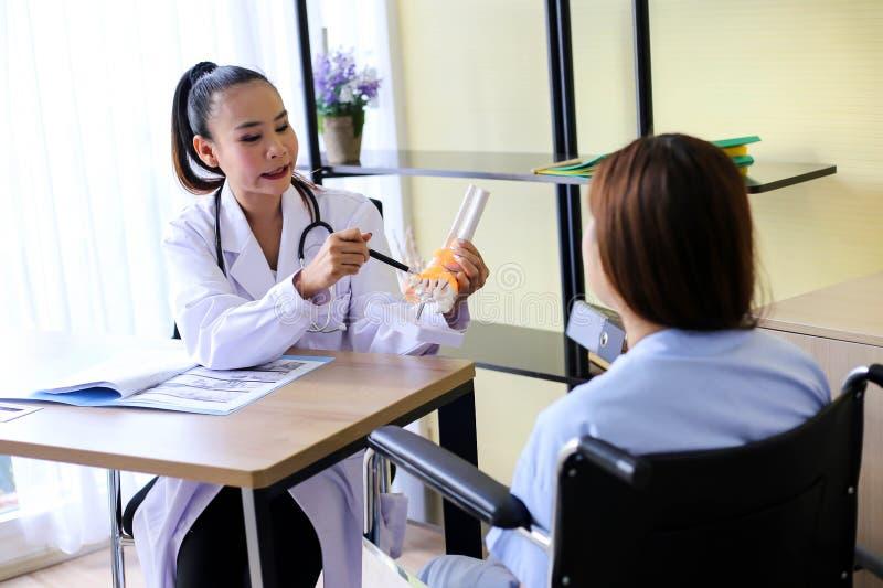 O doutor bonito da mulher está apontando em um osso na espinha a disposição da articulação do joelho com paciente fotografia de stock