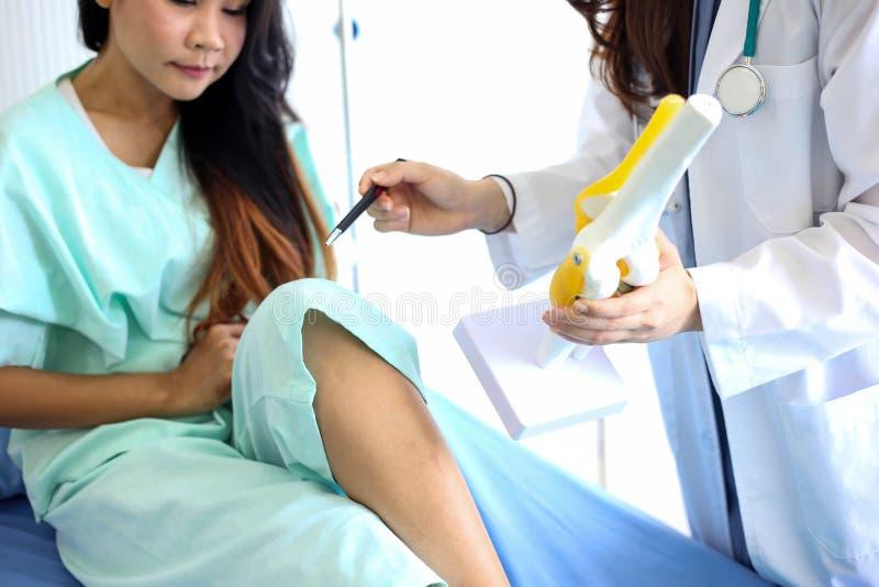 O doutor bonito da mulher está apontando em um osso na espinha o la imagens de stock