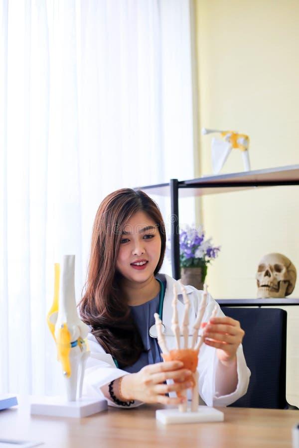 O doutor bonito da mulher está apontando em um osso na espinha o la fotos de stock