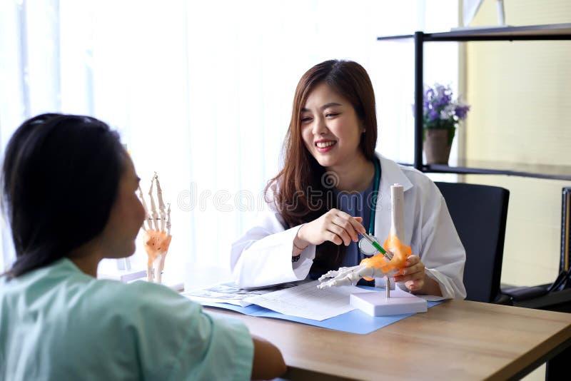 O doutor bonito da mulher está apontando em um osso na espinha o la fotos de stock royalty free