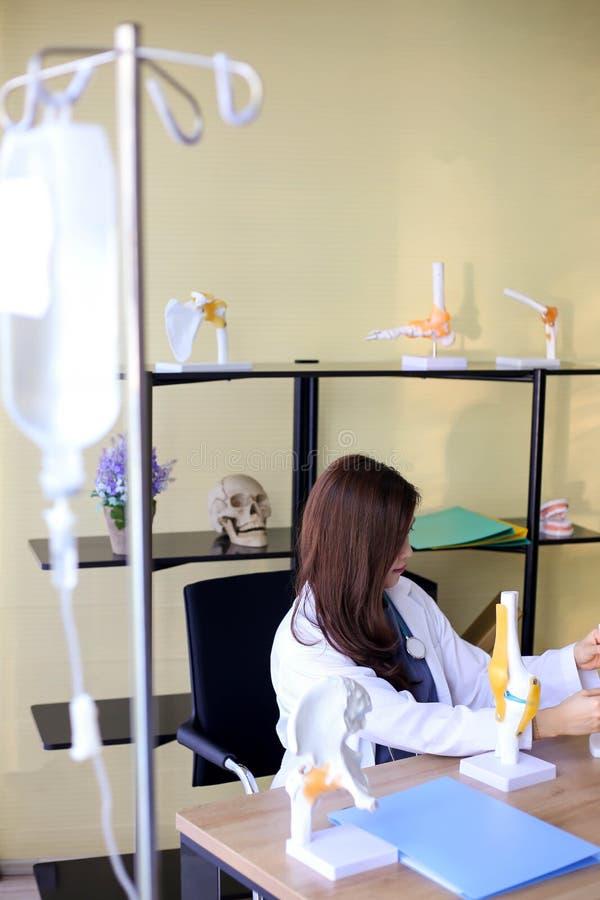 O doutor bonito da mulher está apontando em um osso na espinha o la foto de stock