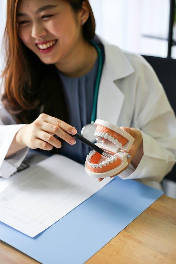 O doutor bonito do dentista da mulher que aponta os dentes modela, verificação dental imagens de stock royalty free