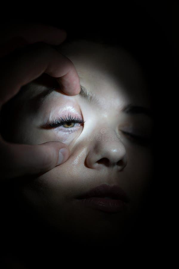 O doutor brilha lanternas elétricas no olho da menina fotografia de stock royalty free