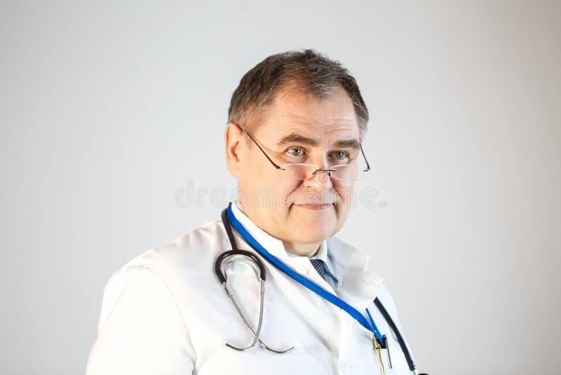 O doutor com um estetoscópio e vidros olha na frente dele fotografia de stock royalty free