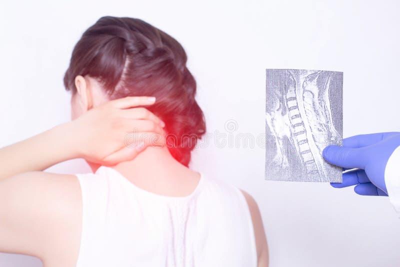 O doutor conduz um exame médico Guarda um exame de raio X de uma menina que tenha a dor no pescoço, comprimindo o nervo fotografia de stock royalty free