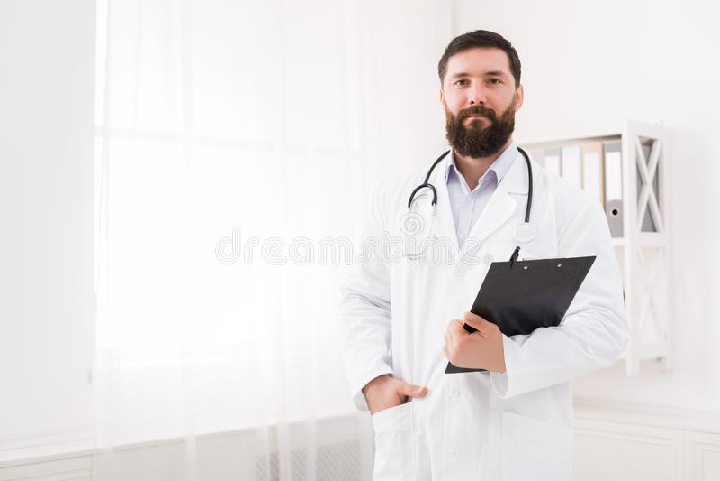 O doutor considerável está recebendo visitantes em seu escritório foto de stock