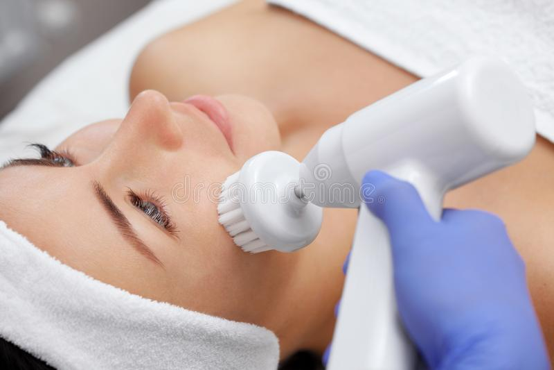 O doutor-cosmetologist faz ao instrumento um procedimento da limpeza da cara do hardware com uma escova de giro macia foto de stock royalty free