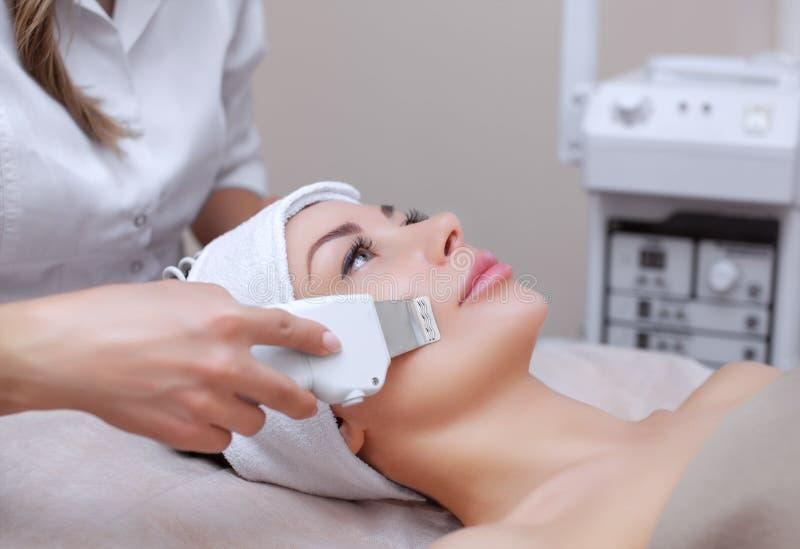 O doutor-cosmetologist faz ao instrumento um procedimento da limpeza do ultrassom da pele facial de um bonito, jovem mulher imagens de stock royalty free