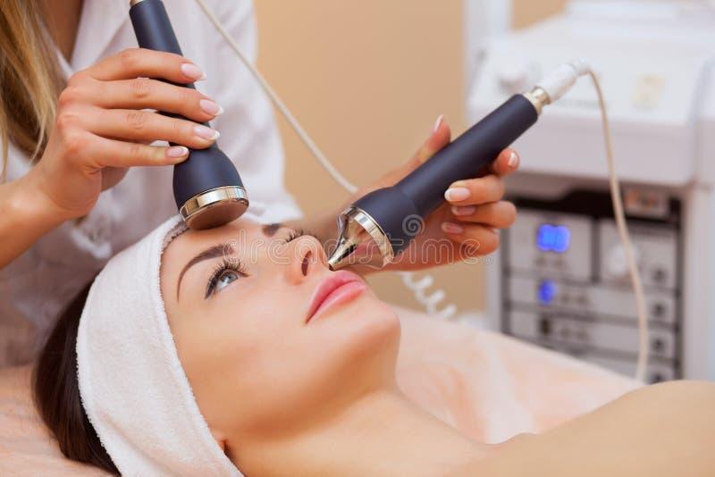 O doutor-cosmetologist faz ao procedimento uma limpeza ultrassônica da pele facial de um bonito, jovem mulher foto de stock