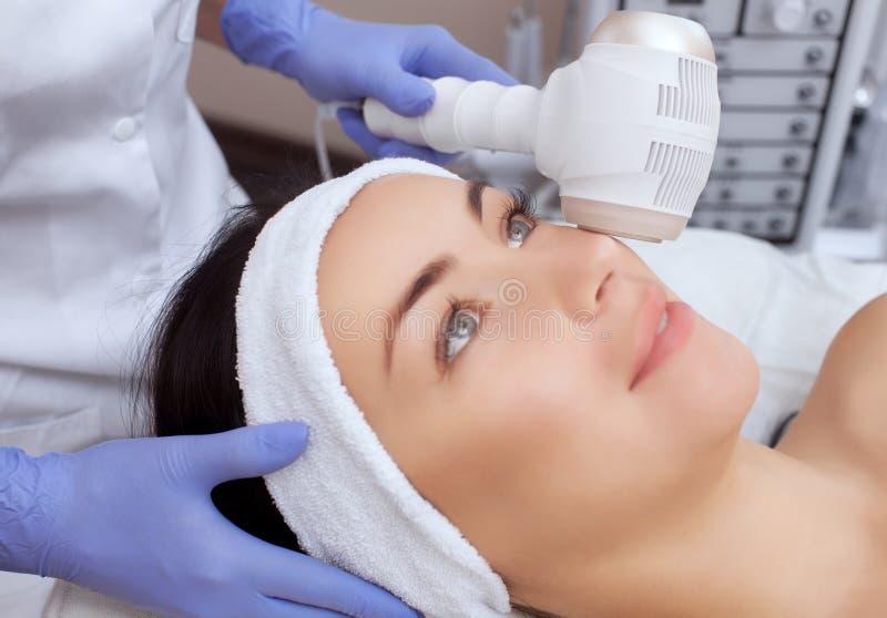 O doutor-cosmetologist faz o procedimento Cryotherapy da pele facial de um bonito, jovem mulher foto de stock