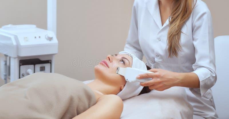 O doutor-cosmetologist faz o procedimento de limpeza do ultrassom da pele facial de um bonito, jovem mulher em um salão de beleza imagens de stock royalty free