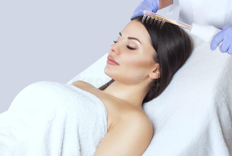 O doutor-cosmetologist faz a terapia de Microcurrent do procedimento no cabelo de um bonito, jovem mulher em um salão de beleza fotos de stock royalty free