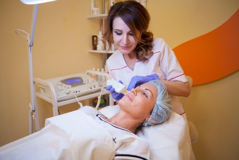 O doutor da cosmetologia faz ao procedimento uma mulher enfrentar a limpeza fotografia de stock