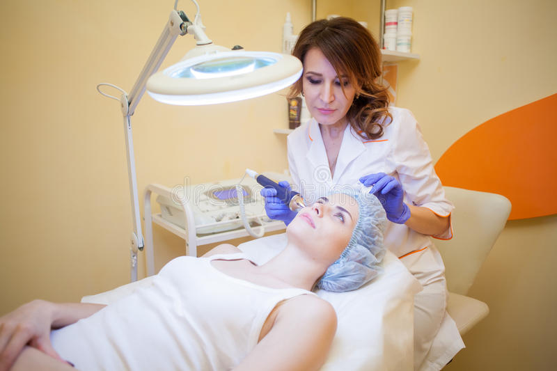 O doutor da cosmetologia faz ao procedimento uma mulher enfrentar a limpeza imagem de stock royalty free