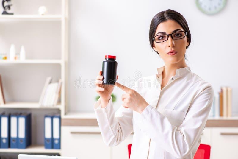 O doutor da mulher com a garrafa das medicinas fotos de stock