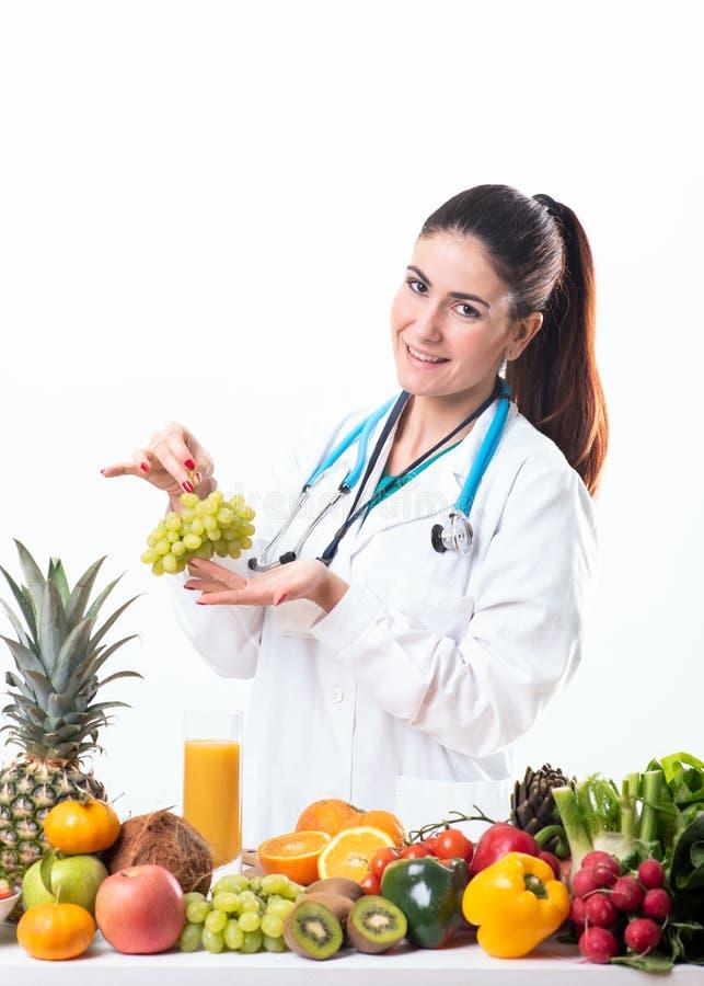 O doutor da nutrição que guarda uma uva frutifica imagens de stock