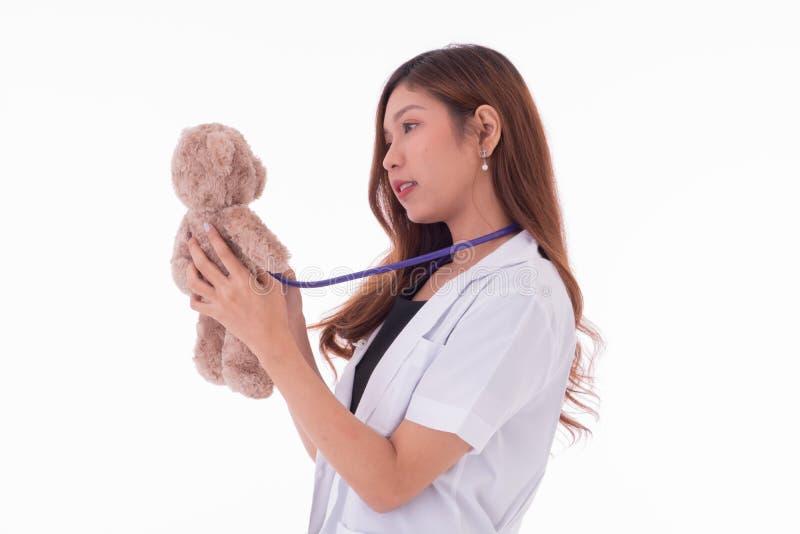 O doutor das mulheres usa o sthethoscope para detectar o urso de peluche imagem de stock
