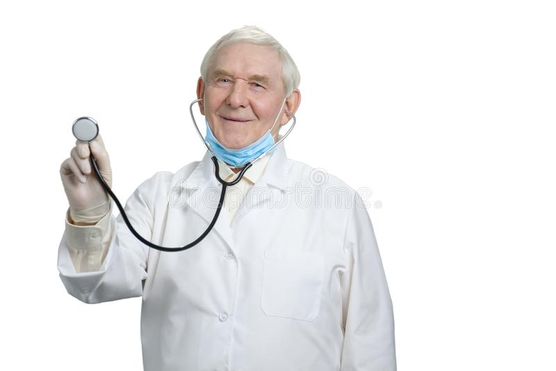 O doutor de sorriso idoso com escuta sua pulsação do coração usando o estetoscópio fotografia de stock