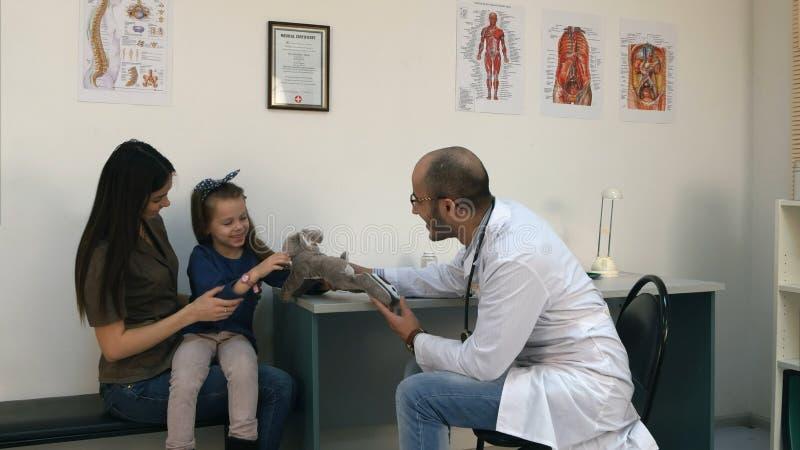 O doutor de sorriso que dá o elogio do brinquedo do coelho virou acima o paciente da menina imagem de stock royalty free
