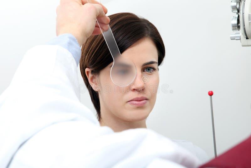 O doutor do ótico do optometrista examina a visão do paciente da mulher foto de stock royalty free