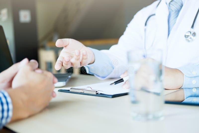 O doutor e o paciente estão discutindo algo, apenas mãos no t foto de stock