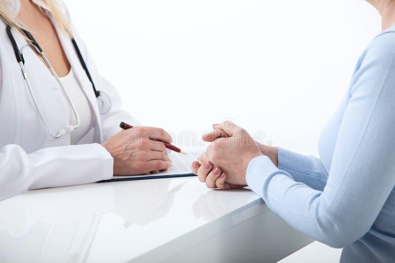 O doutor e o paciente estão discutindo algo, apenas mãos no fim da tabela acima imagem de stock royalty free